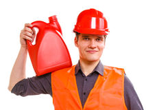 Man worker in safety vest hard hat with canisters. Young man construction worker in orange safety vest and red hard hat holding plastic canisters isolated on Stock Image