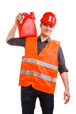 Man worker in safety vest and hard hat with canisters. Young man construction worker in orange safety vest and red hard hat holding plastic canisters isolated on Royalty Free Stock Photography