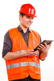 Man worker in safety vest hard hat using tablet. Young man construction worker builder in orange safety vest and red hard hat using tablet touchpad isolated on Royalty Free Stock Photography