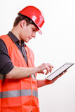 Man worker in safety vest hard hat using tablet. Young man construction worker builder in orange safety vest and red hard hat using tablet touchpad isolated on Royalty Free Stock Photo