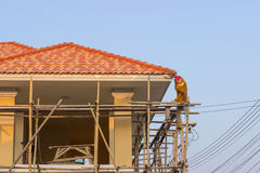 Man worker on scaffold painting roof Stock Photography