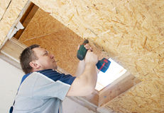 Man worker twists the screw into the ceiling with a screwdriver Stock Photo