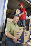 Man With Worker Unloading Truck Of Cardboard Boxes royalty free stock image