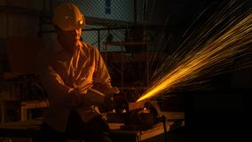 Man worker uses grinding cutting machine to cut metal, focus. The man worker uses grinding cutting machine to cut metal, focus on flash light line of sharp spark Royalty Free Stock Photo