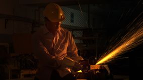 The man worker uses grinding cutting machine to cut metal. Focus on flash light line of sharp spark,in low Light Stock Photo