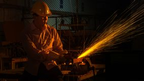 The man worker uses grinding cutting machine to cut metal. Focus on flash light line of sharp spark,in low Light Stock Image