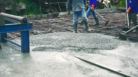 Man worker using a concrete steel basket for cement after Pouring ready-mixed concrete. On steel reinforcement to make the road by mixing mobile the concrete stock footage