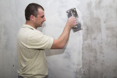 Man worker using float to apply first layer of putty Royalty Free Stock Photos