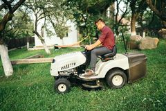 Man worker using garden lawn mower and cutting grass. Male worker using garden lawn mower and cutting grass Stock Photos