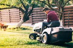 Man worker using ride-on lawnmower and cutting grass through garden. Male worker using ride-on lawnmower and cutting grass through garden Royalty Free Stock Image