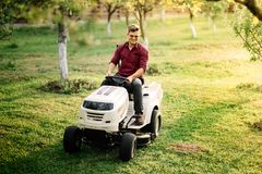 Man worker using ride on lawnmower, male riding lawn tractor and relaxing during sunset golden hour Stock Image