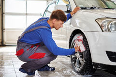 Man worker washing car`s alloy rims on a car wash Stock Images
