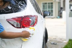 Man worker washing car`s alloy wheels on a car wash.  stock image