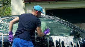 Man worker washing car with sponge on a car wash stock video