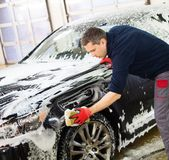 Man worker washing luxury car. With sponge on a car wash Royalty Free Stock Photography