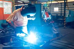 Man or worker welding metal part at factory with very smoke and sparkle bright right royalty free stock photo