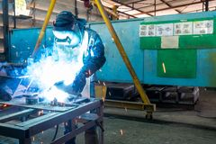 Man or worker welding metal part at factory with very smoke and sparkle bright right royalty free stock image
