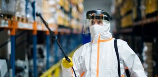 Free Man Worker With Protective Mask And Suit Disinfecting Industrial Factory With Spray Gun. Royalty Free Stock Photo - 183247385