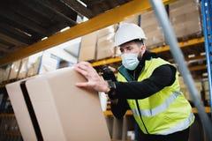 Man worker working indoors in warehouse, coronavirus concept.