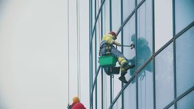 A man worker in yellow work clothes hanging on ropes and wipes the exterior windows of a business skyscraper - holding