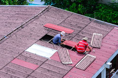 Man workers replacing damaged old tiles roof Royalty Free Stock Image