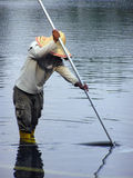 Man working. A South-East Asian man doing maintenance work on a pond Royalty Free Stock Image