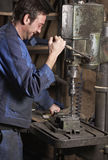 Man working. Mid adult man working at drill machine at industrial workshop royalty free stock image