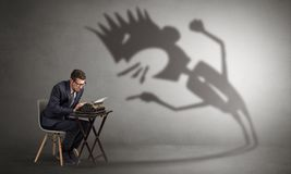 Man working and he is afraid of a yelling shadow. Man working hard and he is afraid of a yelling shadow Royalty Free Stock Photos