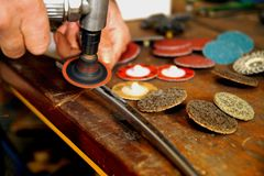 A man working with air pump grinder cleans metal parts blanks. royalty free stock photo