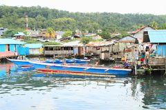 Man working on anchored boat in Manokwari. Men sitting and working on traditional boat anchored on sea by fishermen village while other men watching him and stock images