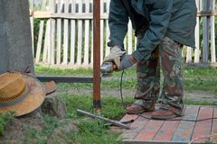 A man working with angle grinder in the backyard royalty free stock photography