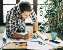Man working on architectural project. Young man working on architectural project. Modern home office concept for freelance professions Stock Images