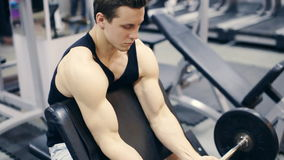 Man working arms at gym, he lifting bells and working his biceps, slow motion stock video footage