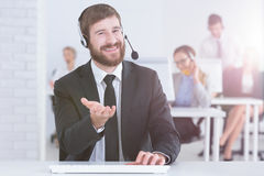 Man working as customer service representative. Young men in a suit working as customer service representative Stock Photos