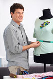 Man working as fashion designer. With dress doll in his studio Royalty Free Stock Photo