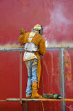Man Working as a Welder. Welder concentrate working on a red tank Royalty Free Stock Photo
