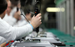 Man working on assembly line. Assembling TV sets using electric screwdriver Royalty Free Stock Photography