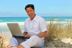 Man working on the beach. Man working on the beach using a laptop Royalty Free Stock Images