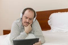 Man working in bed Royalty Free Stock Image
