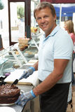Man Working Behind Counter In Cafe Slicing Cake. Smiling At Camera Stock Image