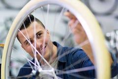 Man working in bicycle repair shop Royalty Free Stock Images