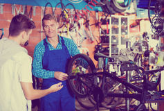 Man working with bicycles wheel and helping boy Royalty Free Stock Photo