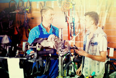 Man working with bicycles wheel and helping boy Stock Photos