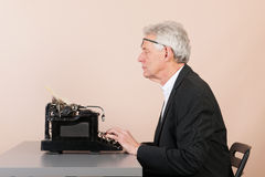 Man working with black typewriter Royalty Free Stock Image