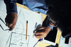 Man working on blueprint in evening stock photo