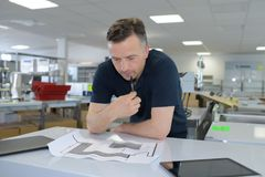 Man working on blueprint in office Royalty Free Stock Image
