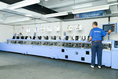 Man working on a brochure and magazine stitching process machine Royalty Free Stock Image