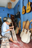Man working on building a hand made guitar at Yogyakarta Stock Images