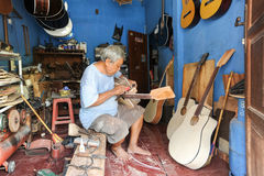 Man working on building a hand made guitar at Yogyakarta royalty free stock photography