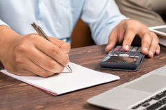 Man working with calculator, business document and laptop comput Stock Photo
